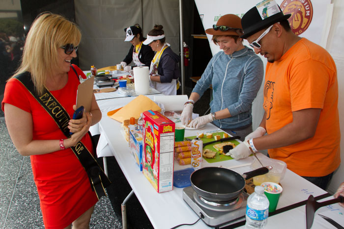 Rachael Narins, Executive Judge, enjoys the ingredients of the sandwich of Cristhian Mace (center) and Moris Machuca at the Last Grilled Cheese Invitational at the Los Angeles Center Studios on Saturday April 12, 2014.  The sandwich, entitled 'Chef Leprechauns's Golden Shower' included Lucky Charms, Twinkies, Truffle oil, and edible gold paint, among other ingredients.